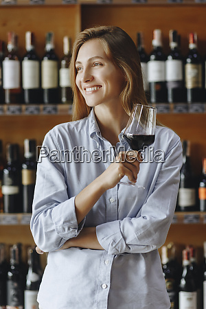 smiling young woman holding glass of