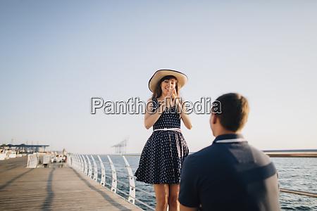 man proposing to woman on pier