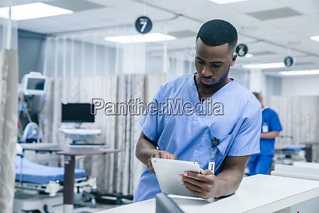 nurse using digital tablet in hospital