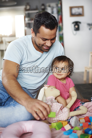 smiling father and baby girl playing