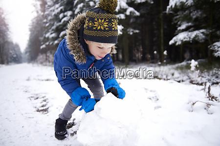 little boy building snowman