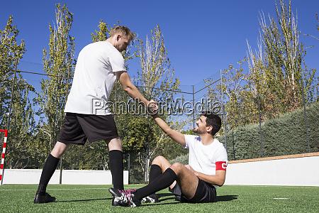 football player helping an injured player