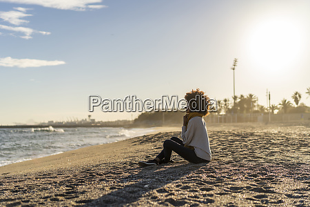woman sitting on the beach at
