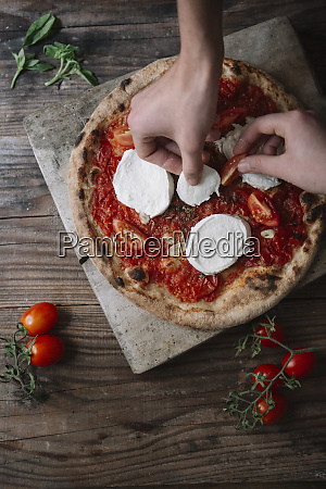 two friends preparing a pizza with