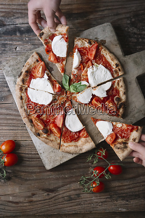 eating, a, pizza, with, mozzarella, , hand - 26912127