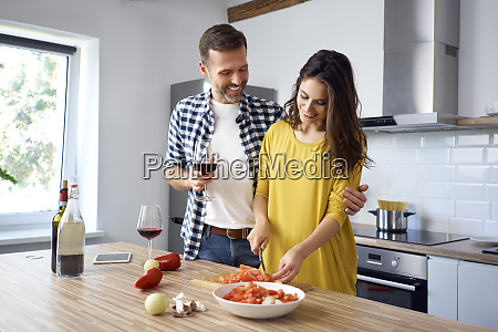 affectionate couple in kitchen preparing spaghetti