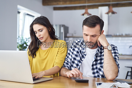 worried couple sitting at dining table