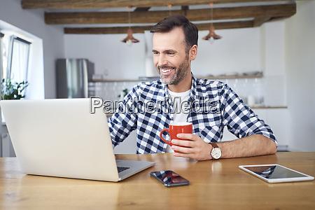 smiling man working remotely on laptop