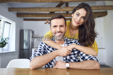 couple embracing sitting at dining table