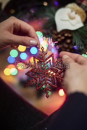 womans hand holding christmas ornament close
