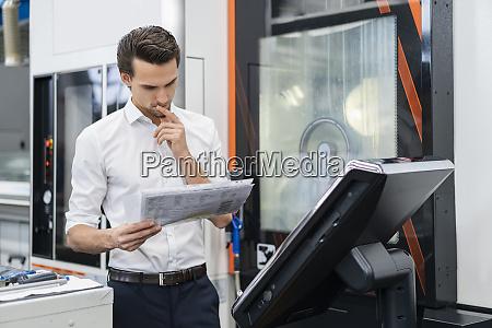 businessman reading manual at a machine
