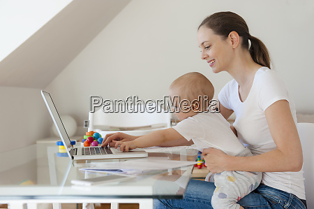 smiling mother and little daughter using