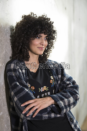 smiling woman leaning against concrete wall