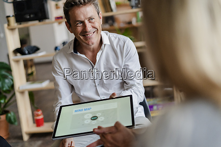 smiling businessman holding tablet with