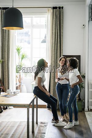 three happy women socializing at home