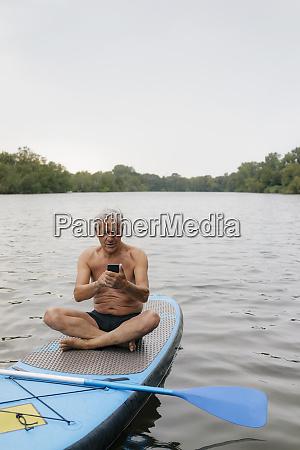 senior man sitting on sup board