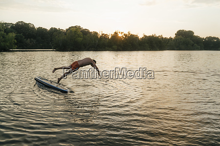 man jumping from sup board