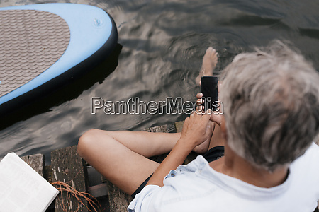 senior man sitting on jetty at