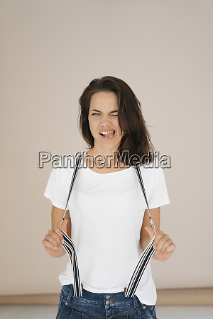 woman pulling funny faces stretching suspenders