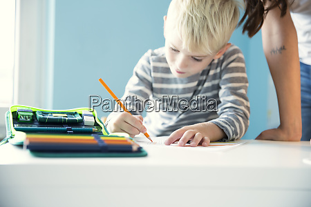 boy doing homework with mother leaning
