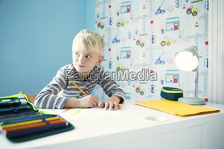 boy doing homework at desk in