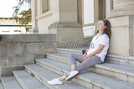 mature woman sitting on stairs in