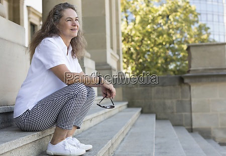 content mature woman sitting on stairs