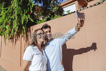 happy couple taking a selfie on