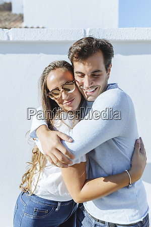 smiling couple hugging on a sunny