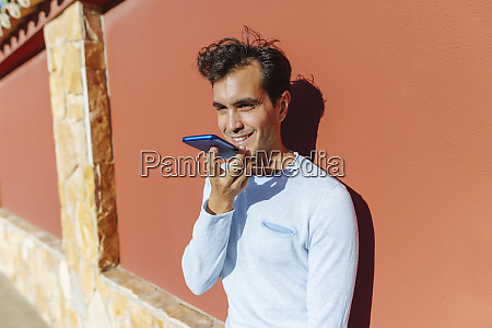smiling man using cell phone on