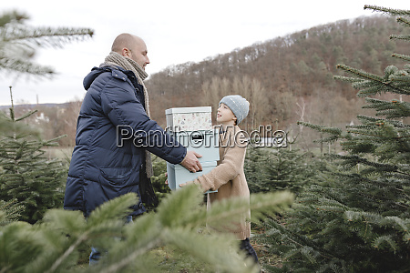father and son carrying gift boxes