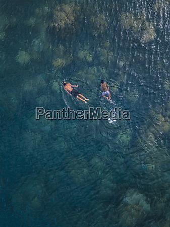 asian boys snorkeling in ocean