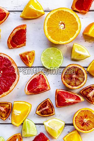sliced citrus fruits on white wood