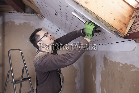 roof insulation worker fixing sarking membrane