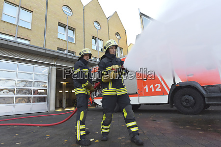 two firefighters standing on yard exercising