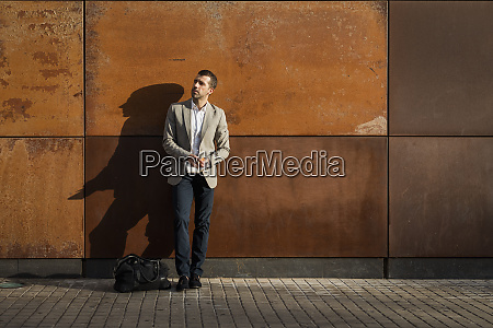 businessman standing at a wall holding