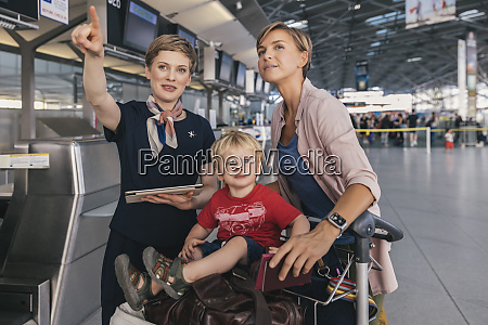 airline employee assisting mother and child