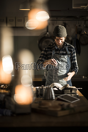 man preparing bread dough in his