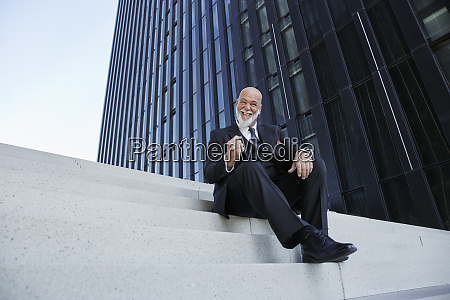 elegant businessman sitting on stairs in