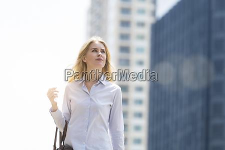 blond woman with handbag walking through