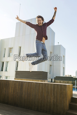 man on a rooftop terrace jumping
