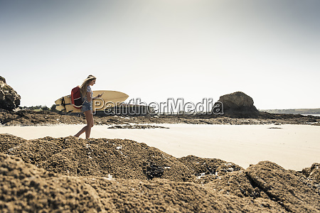 young woman on the beach carrying