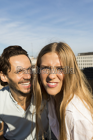 couple on rooftop terrace pulling funny