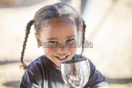 portrait of smiling girl drinking from
