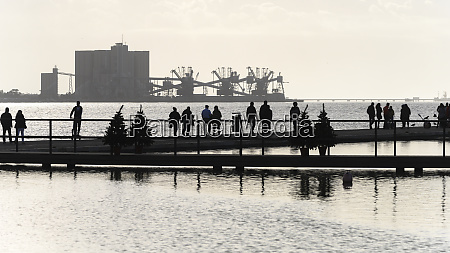 silhouetted pedestrians on a pier on
