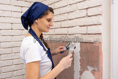 plasterer girl plasters a wall laying