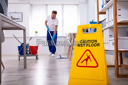 janitor with mop cleaning office