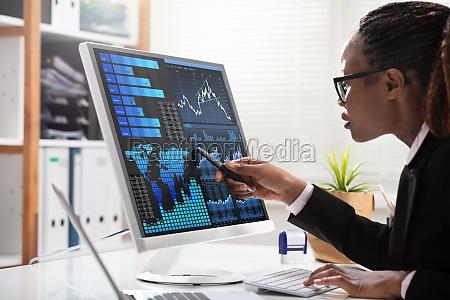 businesswoman analyzing graph on computer