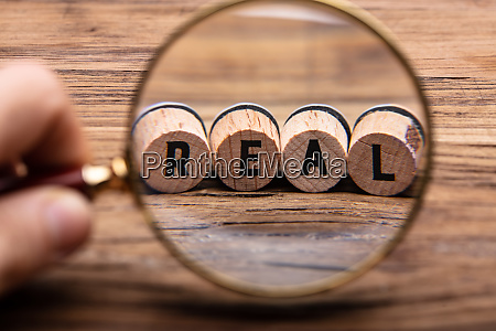 hand holding magnifying glass in front