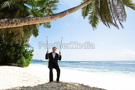 smiling man in formalwear swinging on